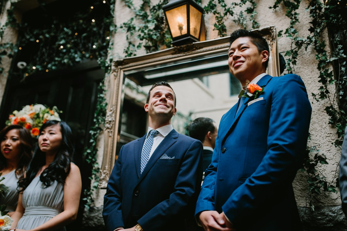 Groomsman in blue suits watch wedding ceremony in Vancouver