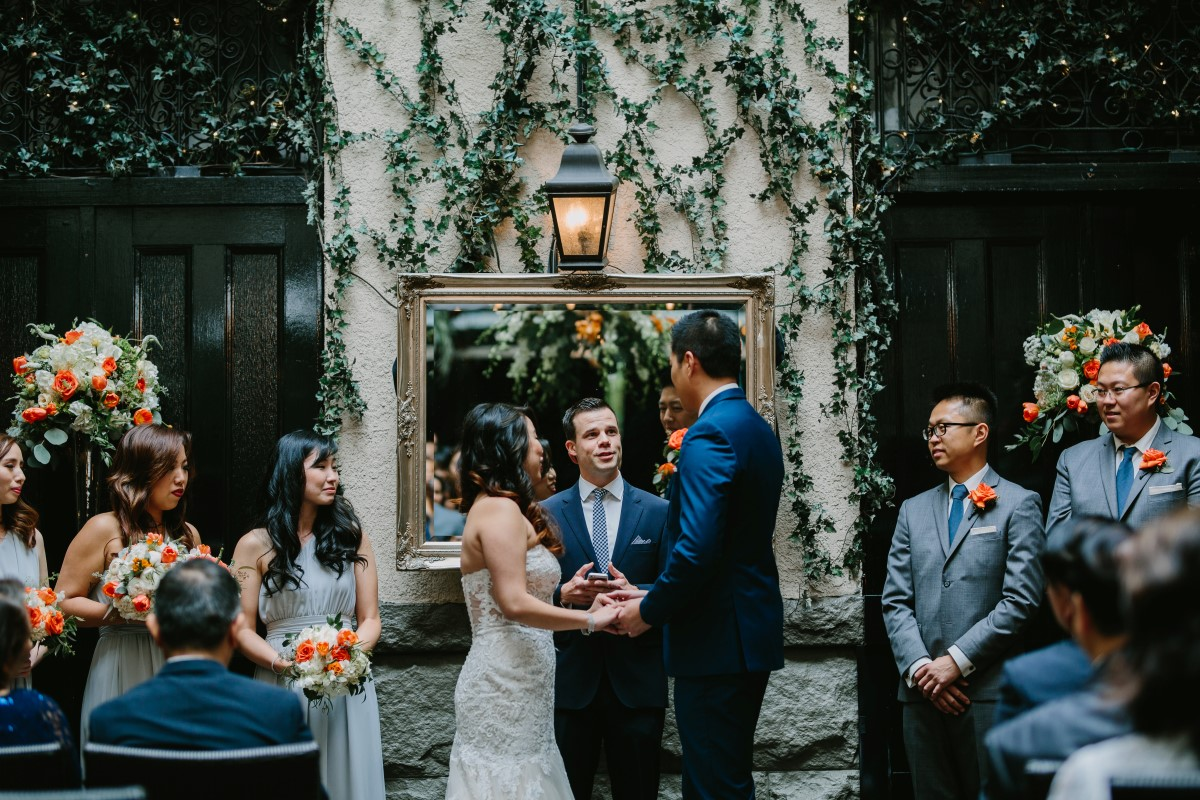 Chinese Fusion Wedding couple exchange vows in front of ivy backdrop in Vancouver