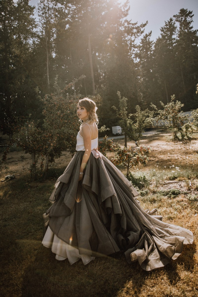 Bride in grey blue overskirt walks through orchard on Vancouver Island