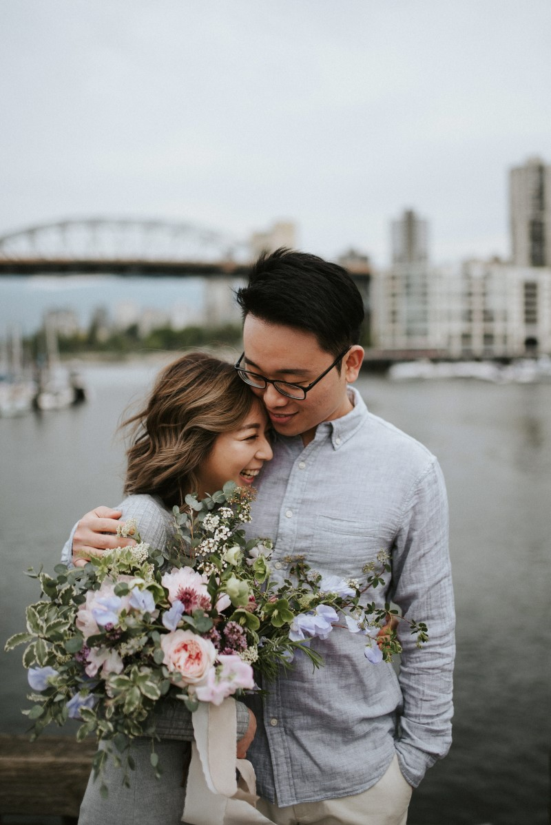 Vancouver Engagement Photo of couple in front of waterfront with bouquet West Coast Weddings Magazine