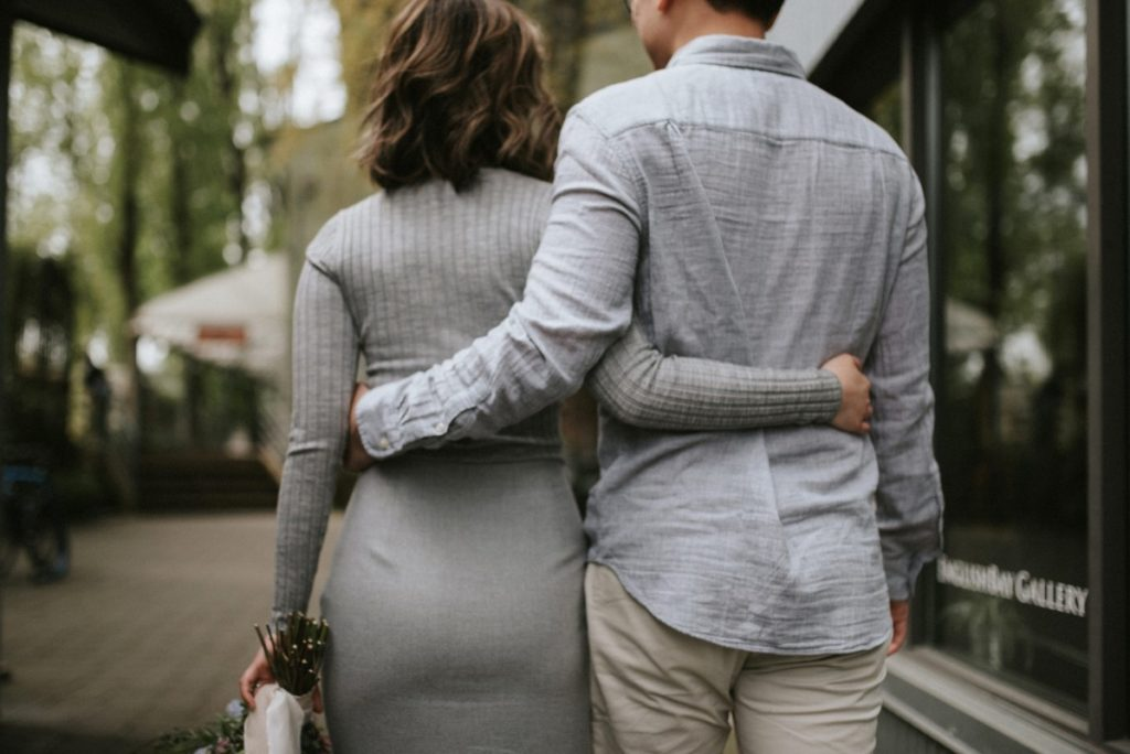 Couple with arms around each celebrate engagement in Vancouver