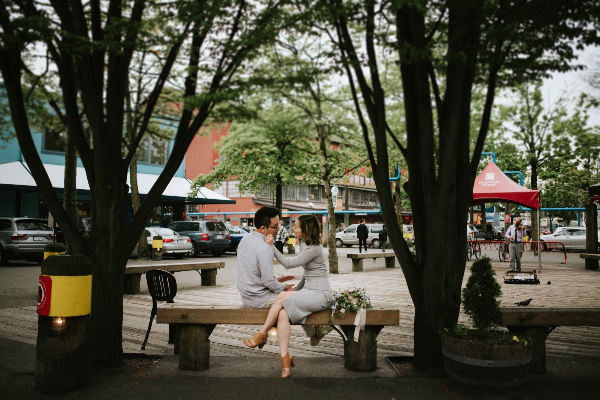 Vancouver Engagement Hari and Kayden sit together on park bench