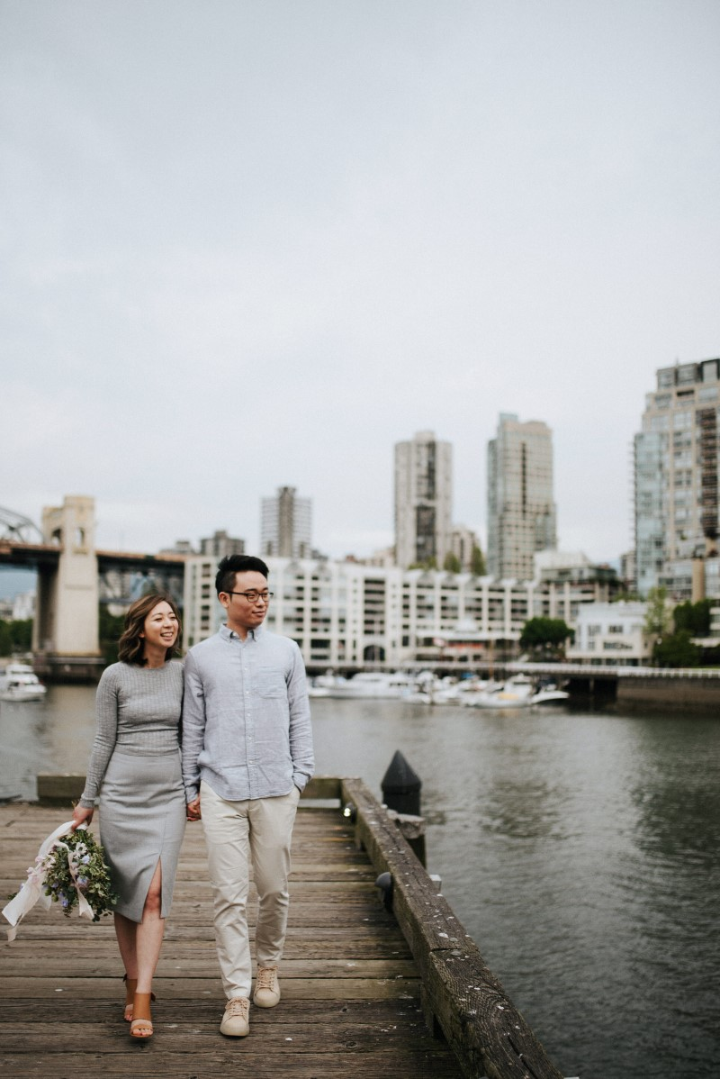 Vancouver Cityscape behind engaged couple who hold hands along the water