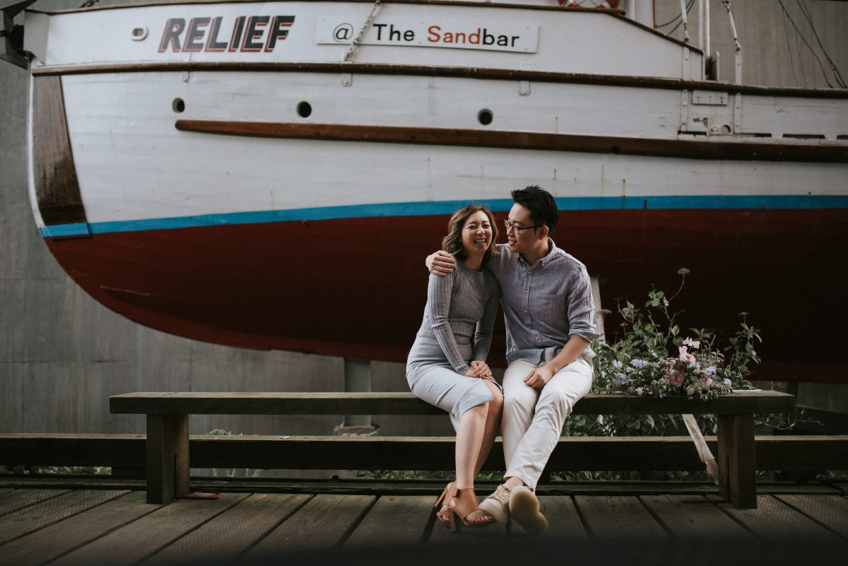 Engaged Couple in front of Wall Paintings in Vancouver Wedding Magazine