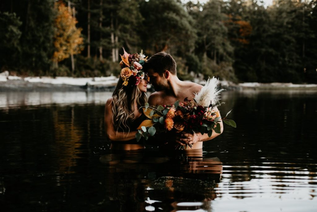 Couple in water with flowers on them