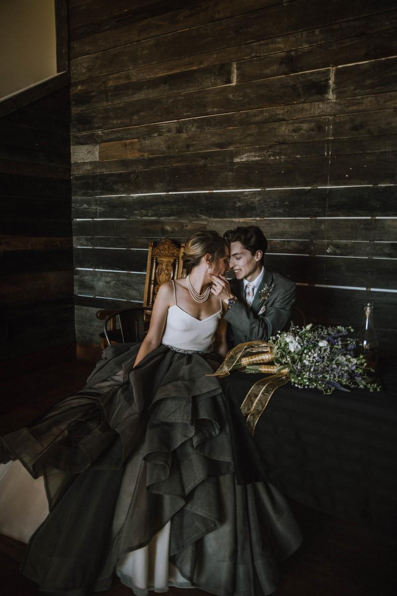 Newlyweds in front of wood wall Vancouver Island Wedding Magazine