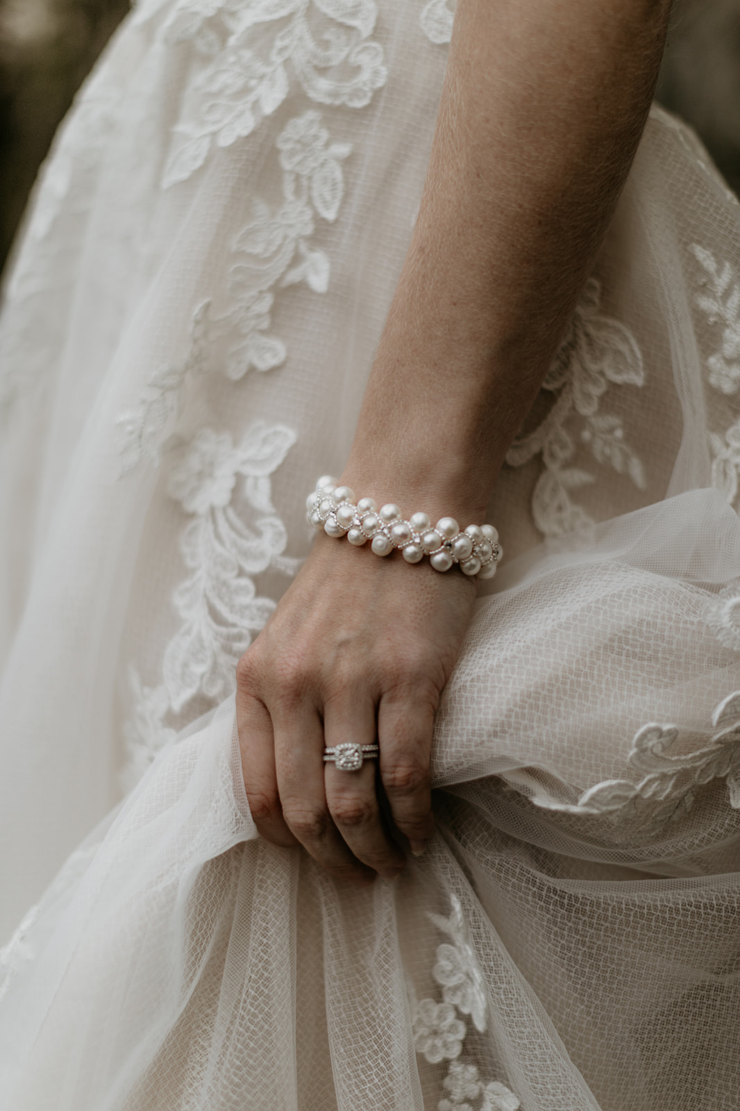 Bride wears pearl bracelet against lace gown on Vancouver Island