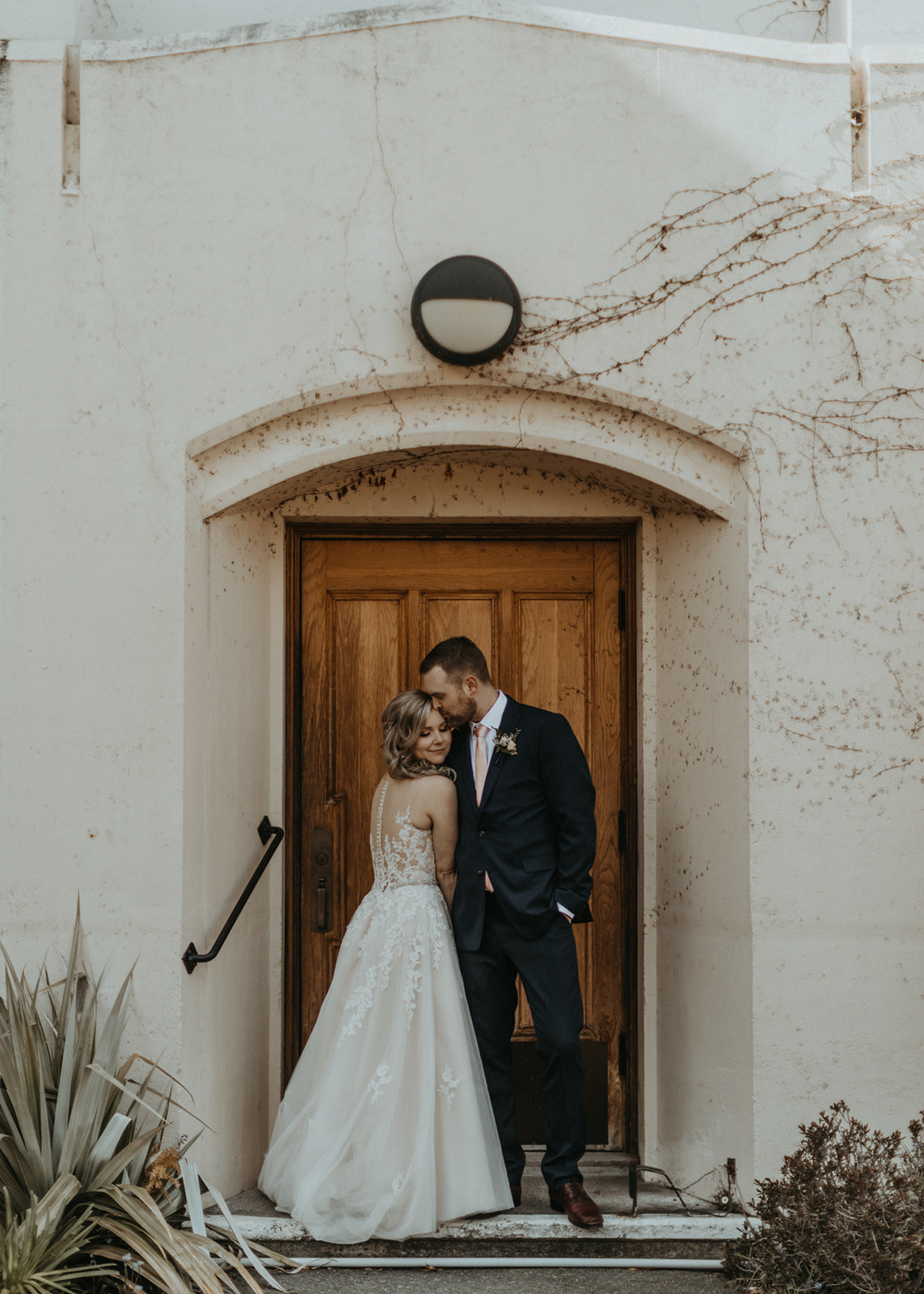 Newlyweds stand together in front of Church Door on Vancouver Island