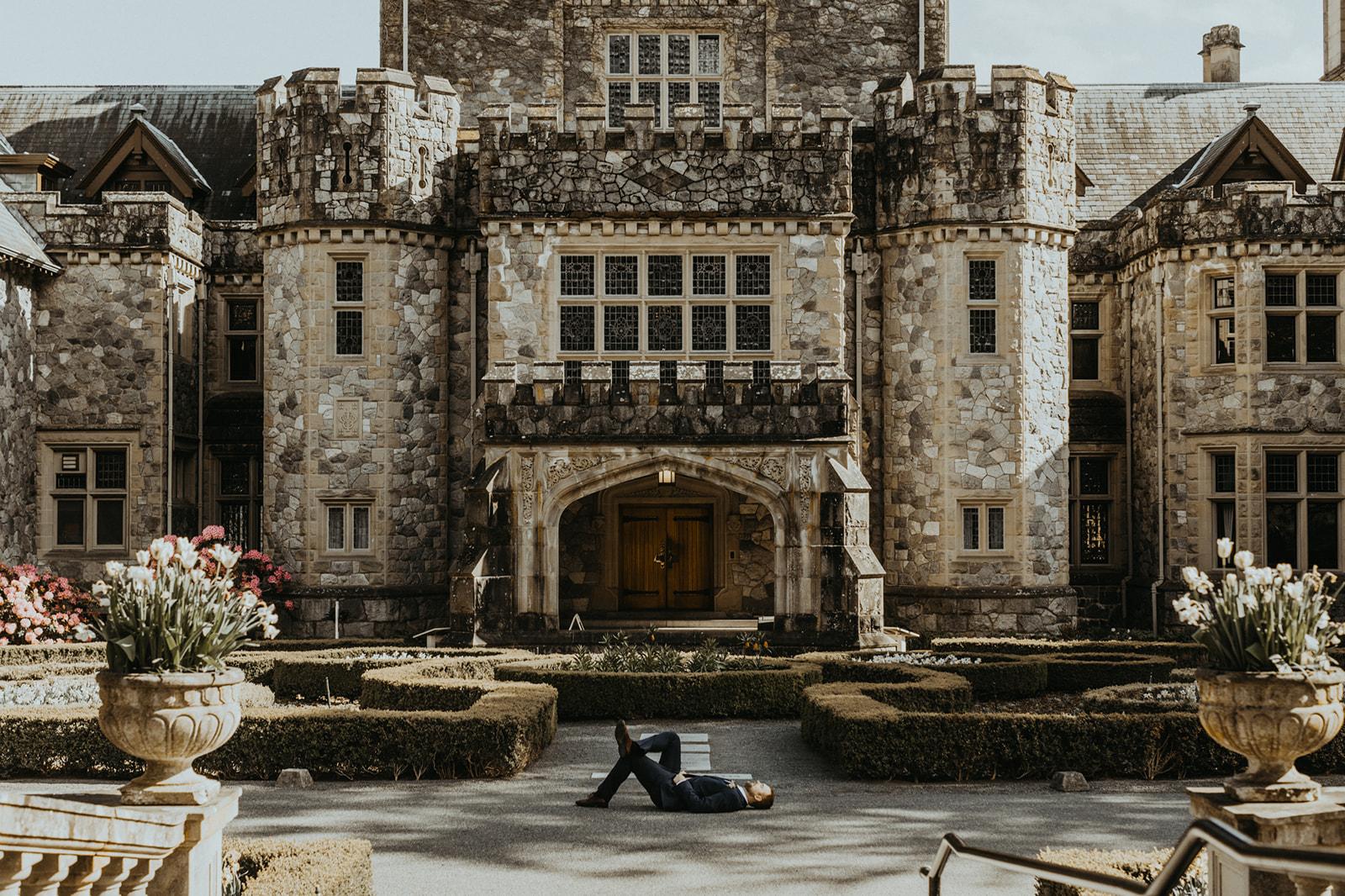 Groom lays on the ground in front of Hatley Castle entrance on Vancouver Island