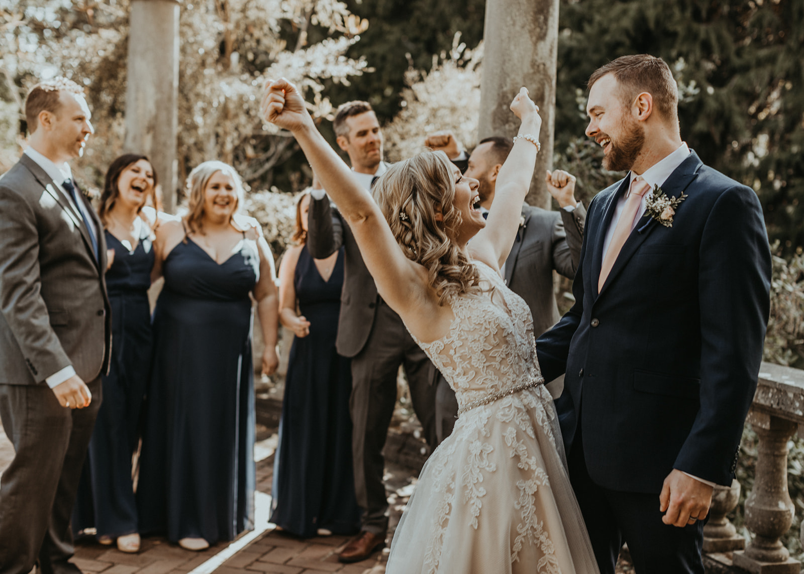 Bride throws her arms up in happiness wearing Rebecca Ingram gown by Blush Bridal Vancouver Island