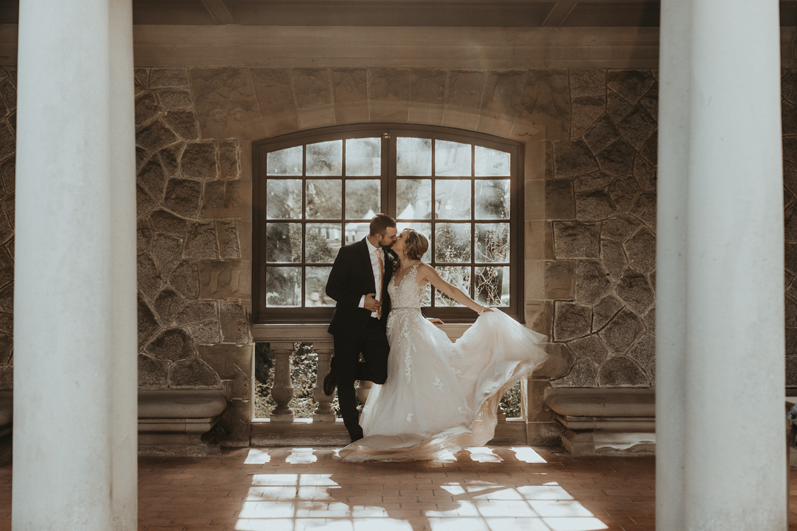 Newlyweds in front of Hatley Castle window as sun pours through on them