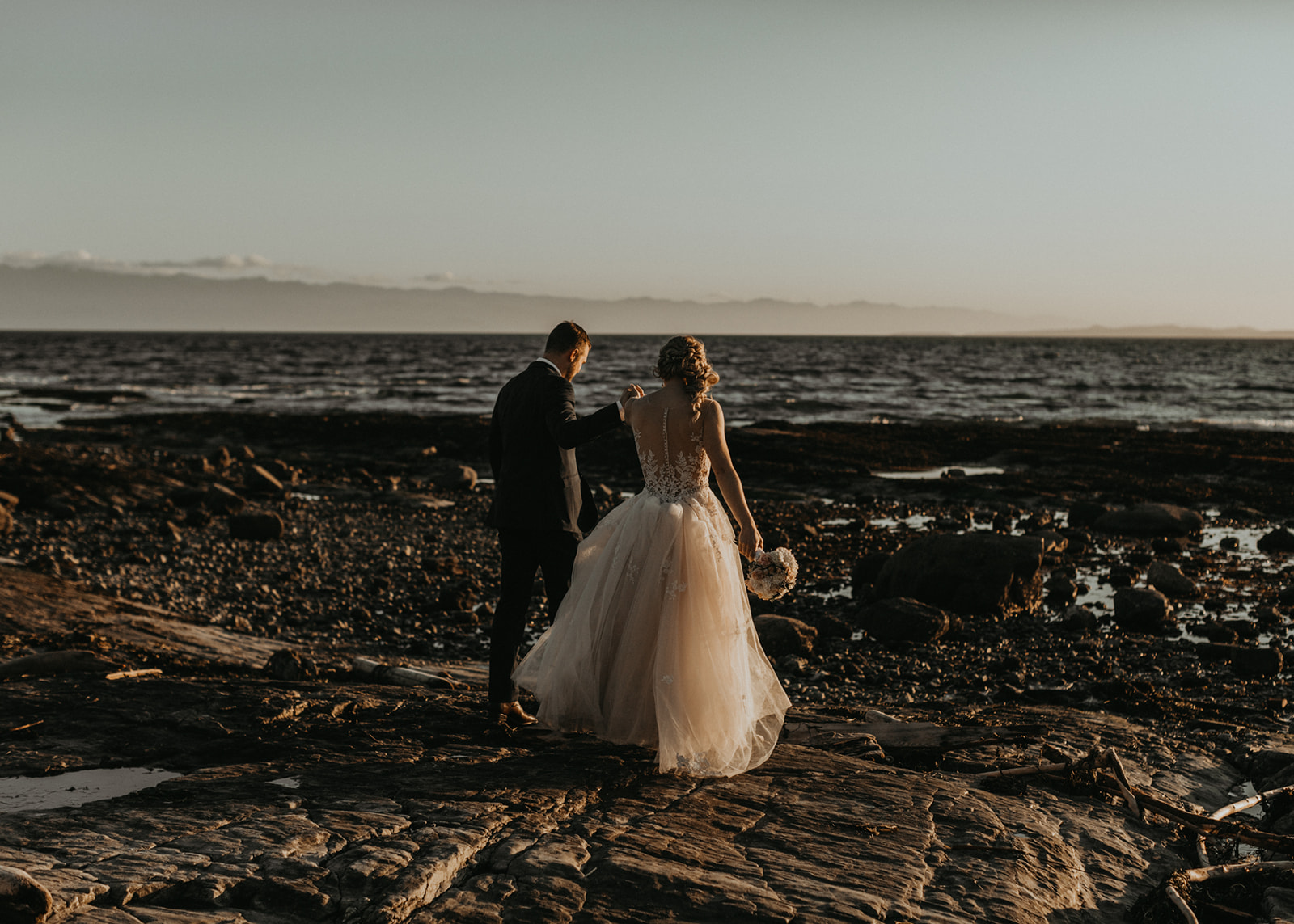 Bride and Groom walk along the rocky beach at reception