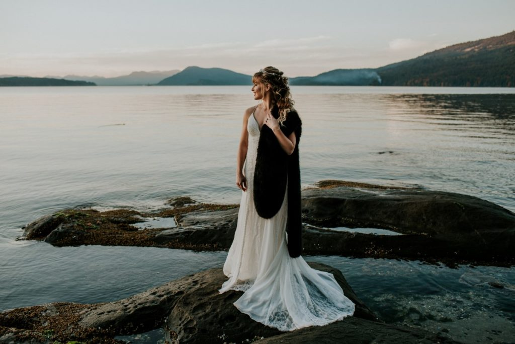 Bride on Beach wearing lace gown and brown fur stole during sunset on Vancouver Island