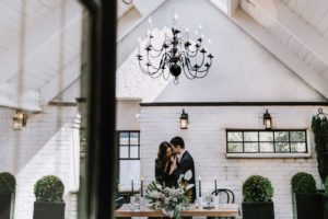 Wrought iron black chandelier in white wall venue with bride and groom