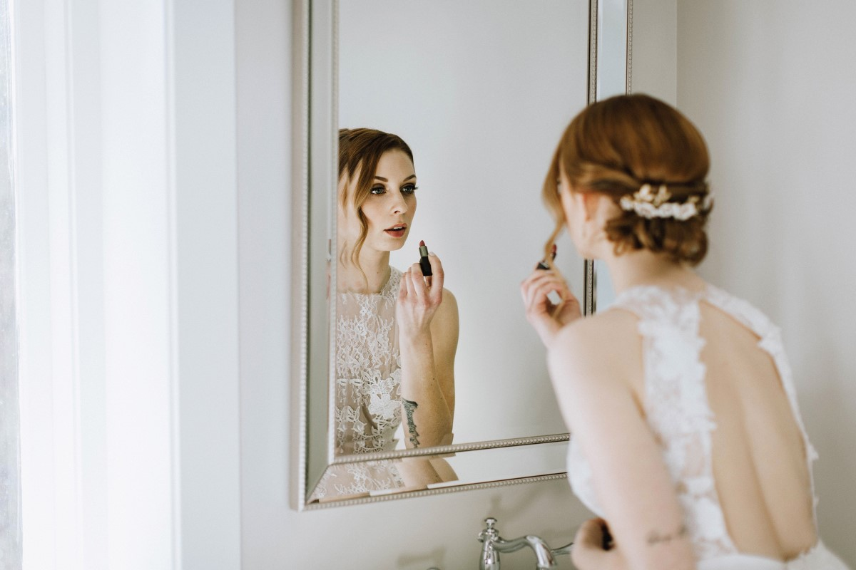 Sophisticated Bride applies lipstick reflected in the mirror Vancouver Island Wedding