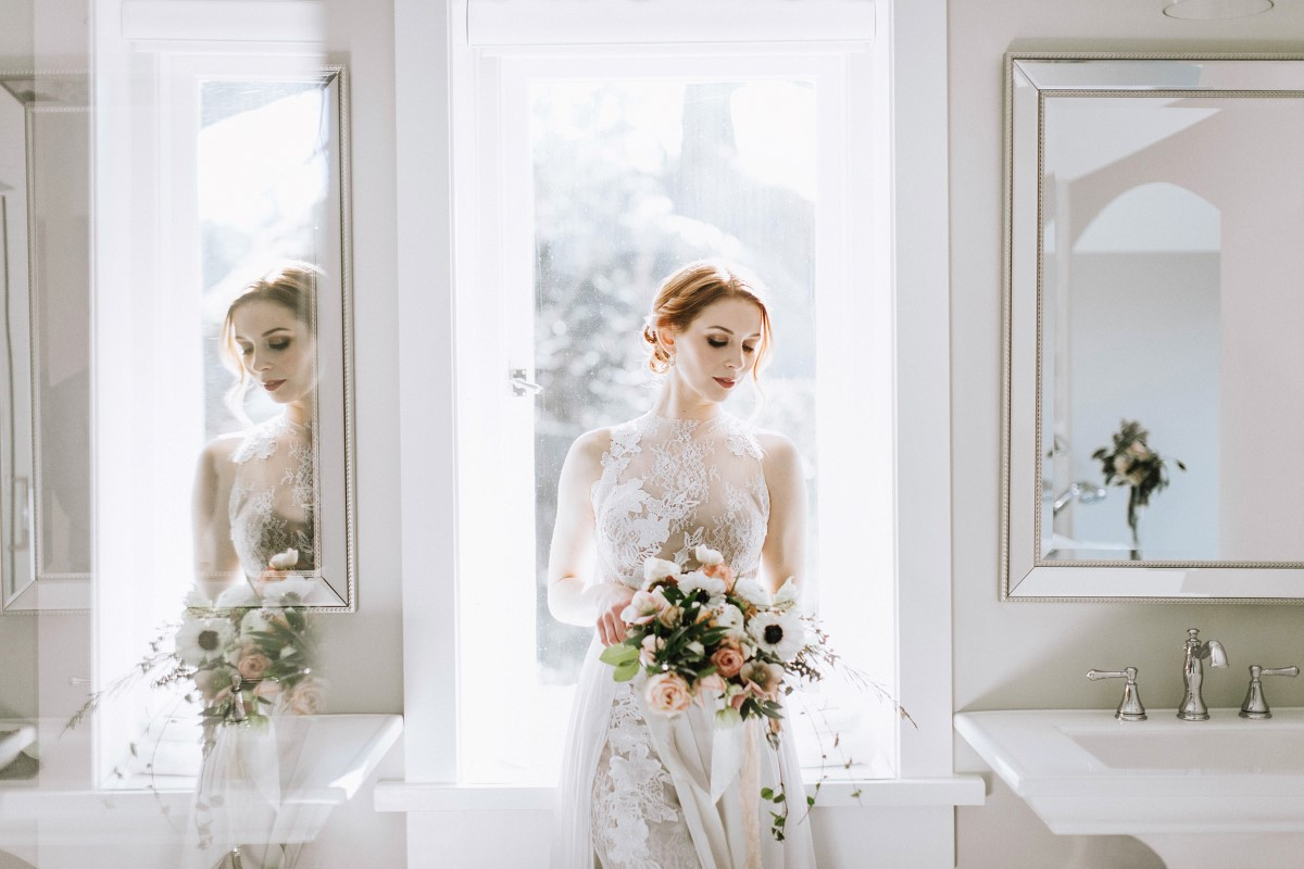 Bride in front of window with gorgeous bouquet by Fleur de Lil Vancouver Island