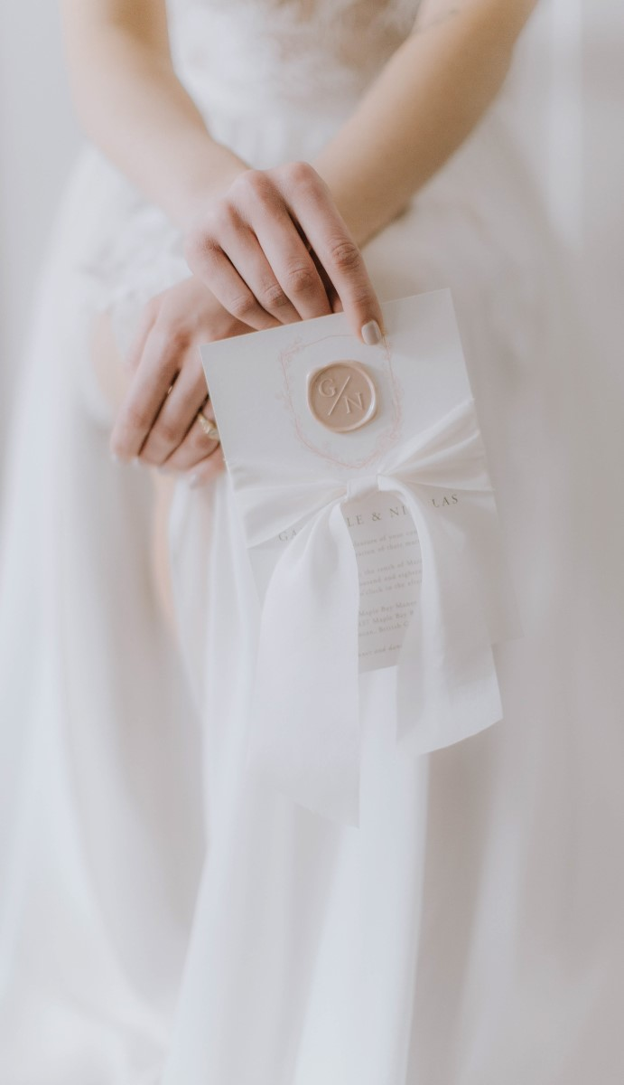 Bride holds white invitation suite with gold wax seal and white ribbon