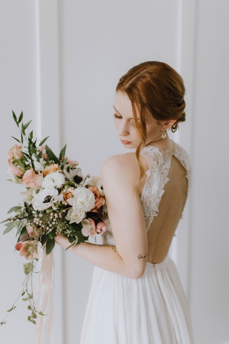 Bride with red hair in chignon and lace cutout back wedding gown