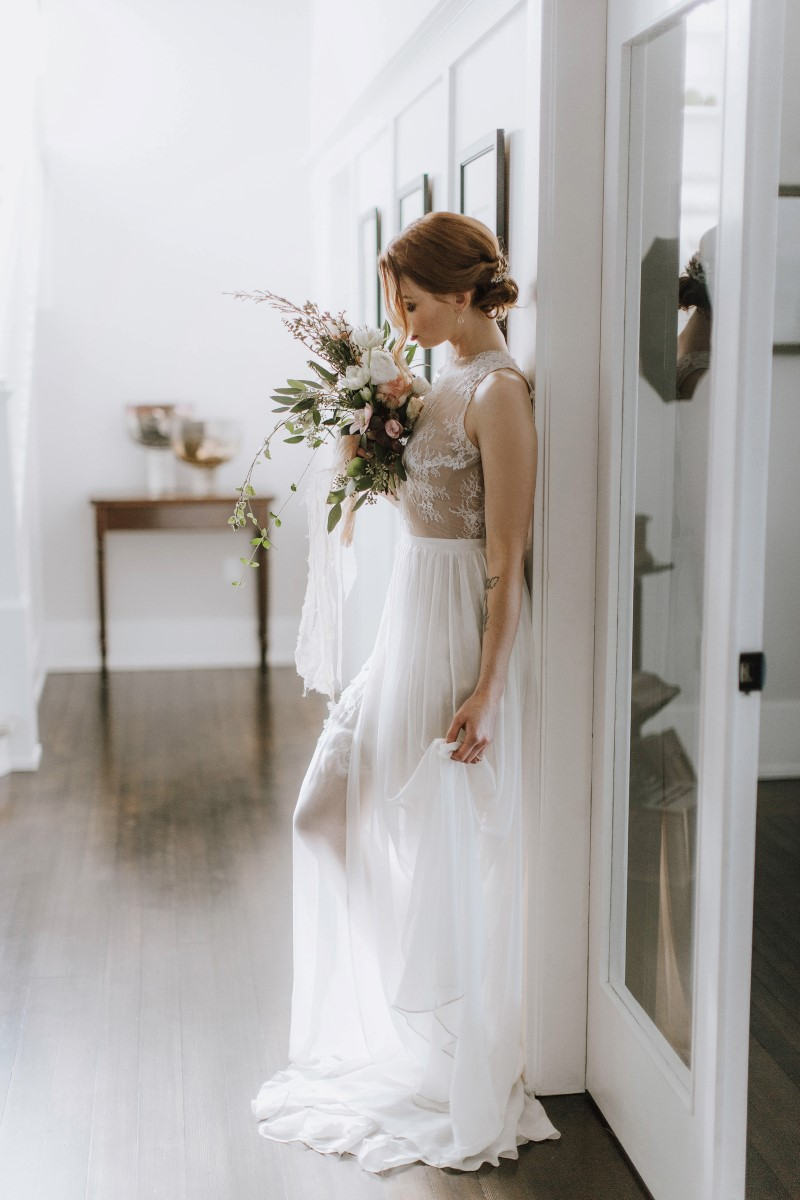 Sophisticated Bride in lace gown and carrying bouquet of greenery and white anemones