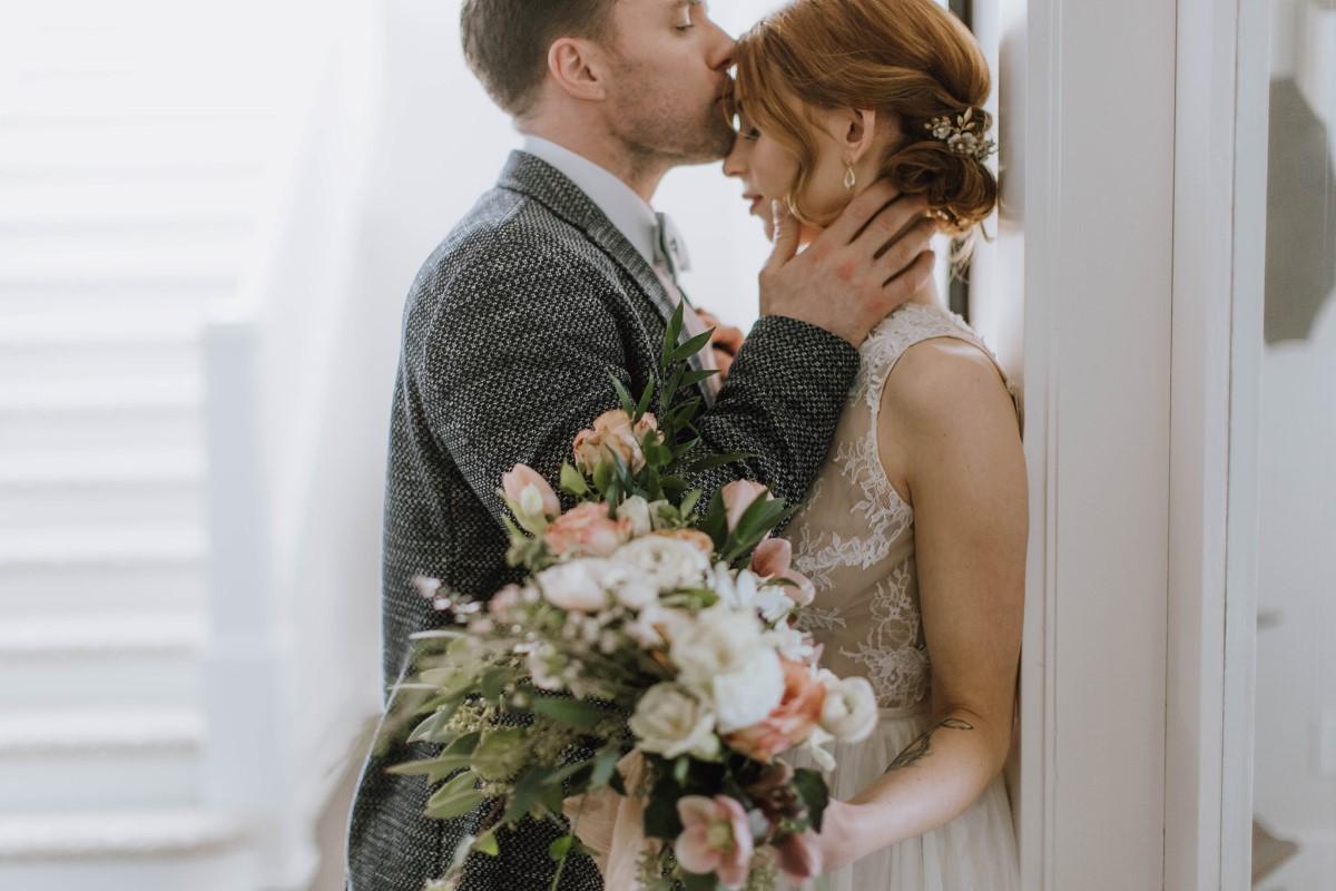 Groom in grey suit kisses bride's forehead