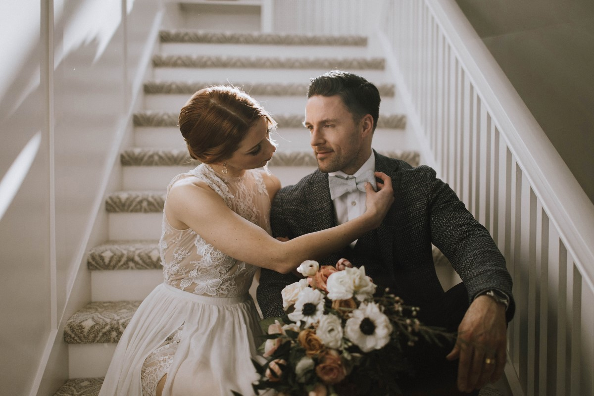 Newlyweds sit on a staircase and hold bridal bouquet at Maple Bay Manor