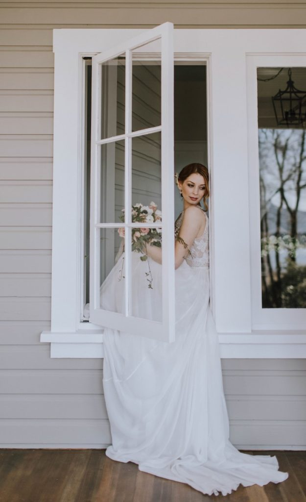 Bride sits on windowsill looking out with dress flowing out the window