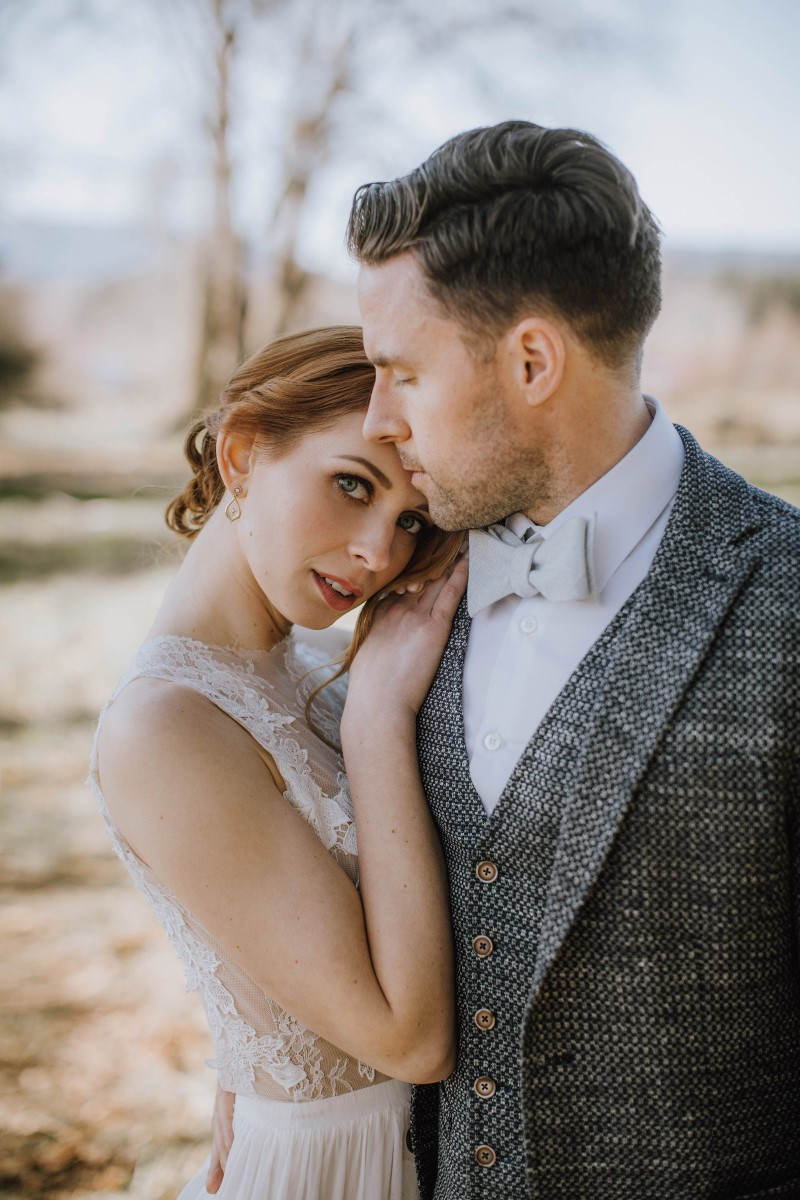 Bride leans on grooms shoulder by Myrtle and Moss Photography