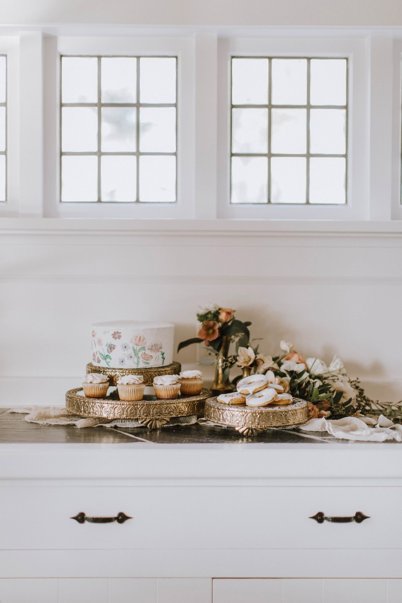 Wedding cake on dessert table with cookies, doughtnuts and floral against white walls