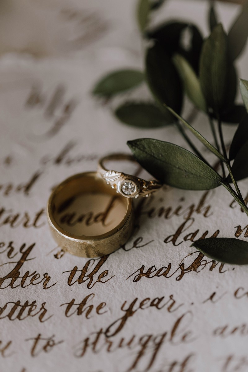 Wedding rings on calligraphy vows and greenery by Vancouver Island Weddings Magazine
