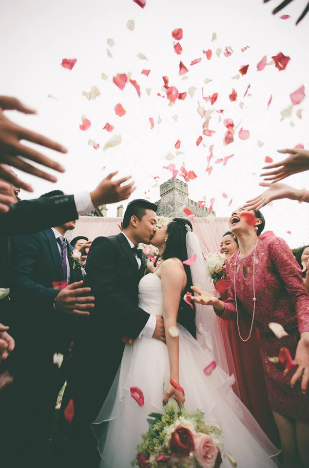 Newlyweds kissing surrounded by family throwing rose petals
