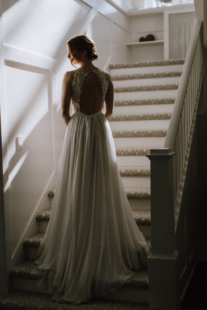 Sophisticated Bride in flowing lace gown on staircase of Maple Bay Manor West Coast Weddings Magazine