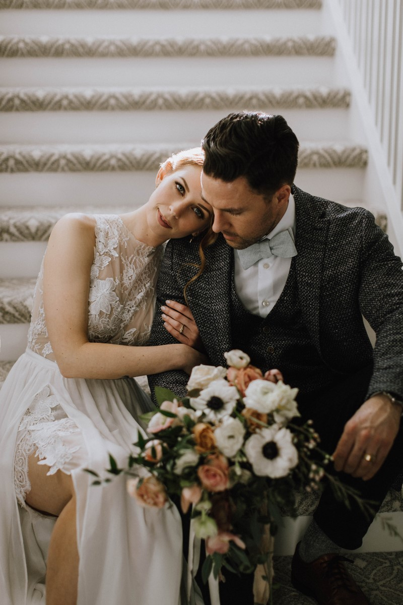Sophisticated Bride leans on groom's shoulder with bouquet