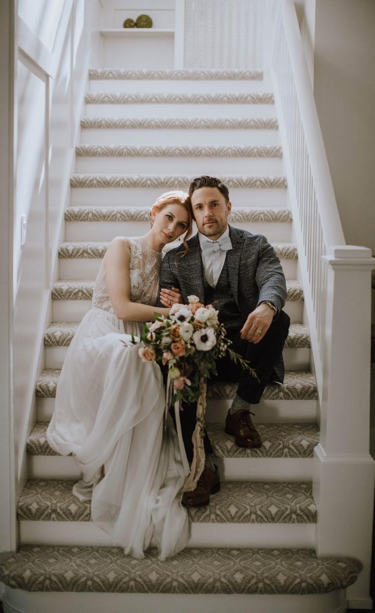 Newlyweds sit on stairs with bouquet West Coast Weddings Magazine