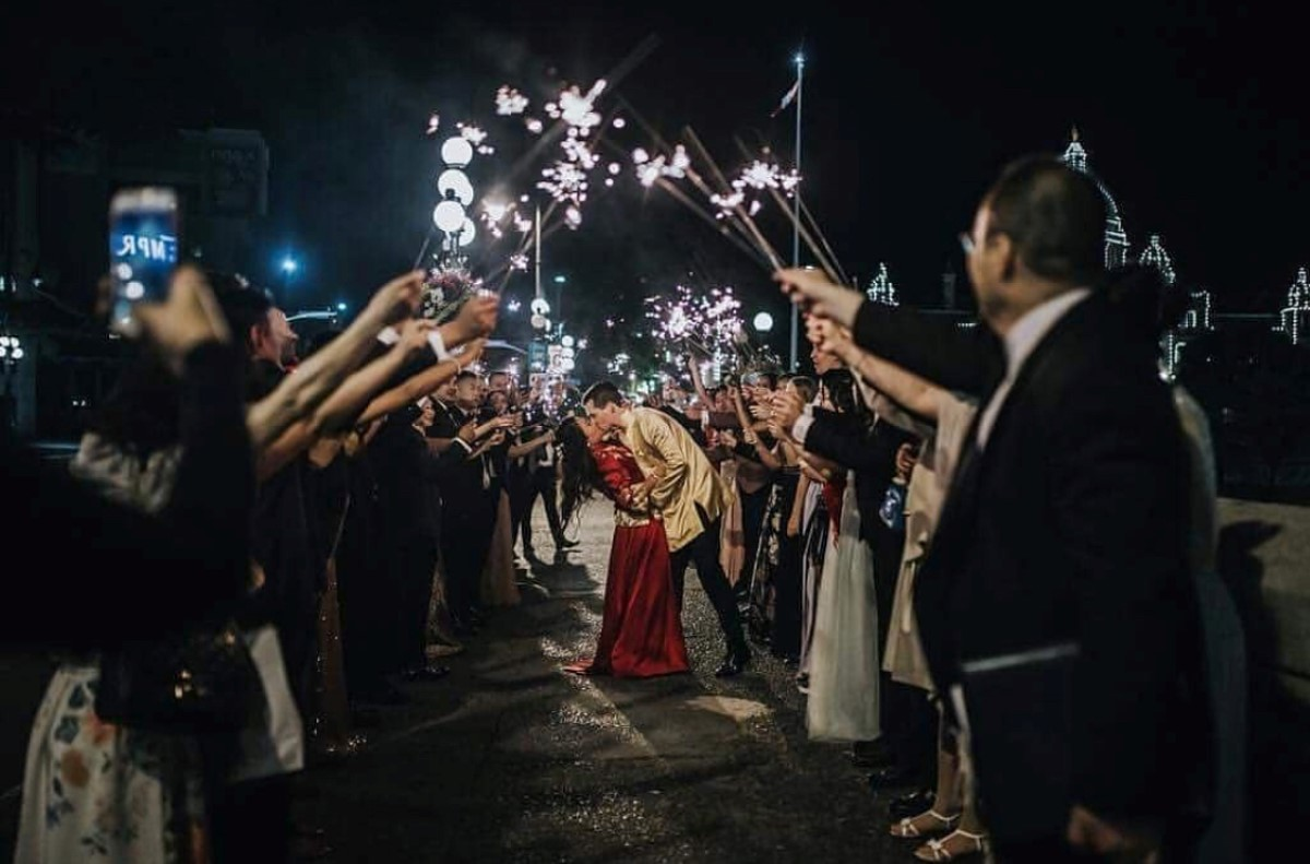 Newlyweds kiss as a guests hold sparklers around them