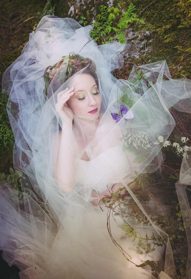 Whimsical Woodland Bride covered with veiling lies in the Vancouver forest