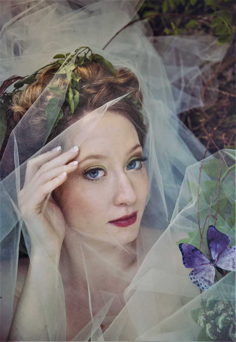 Whimsical Woodland Bride with butterfly in her hair and veil over her face