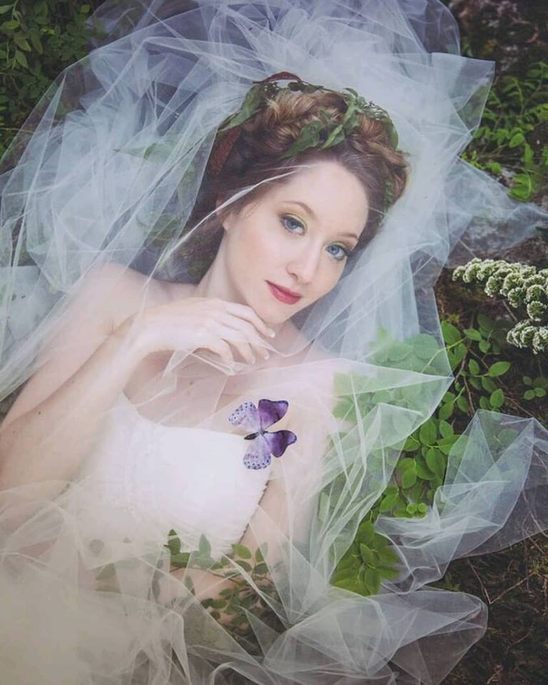 Bride covered with veil has butterfly land on her