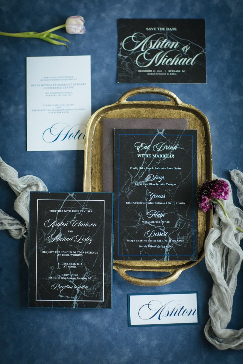 Paper Suite in black with white calligraphy set on rich blue fabric