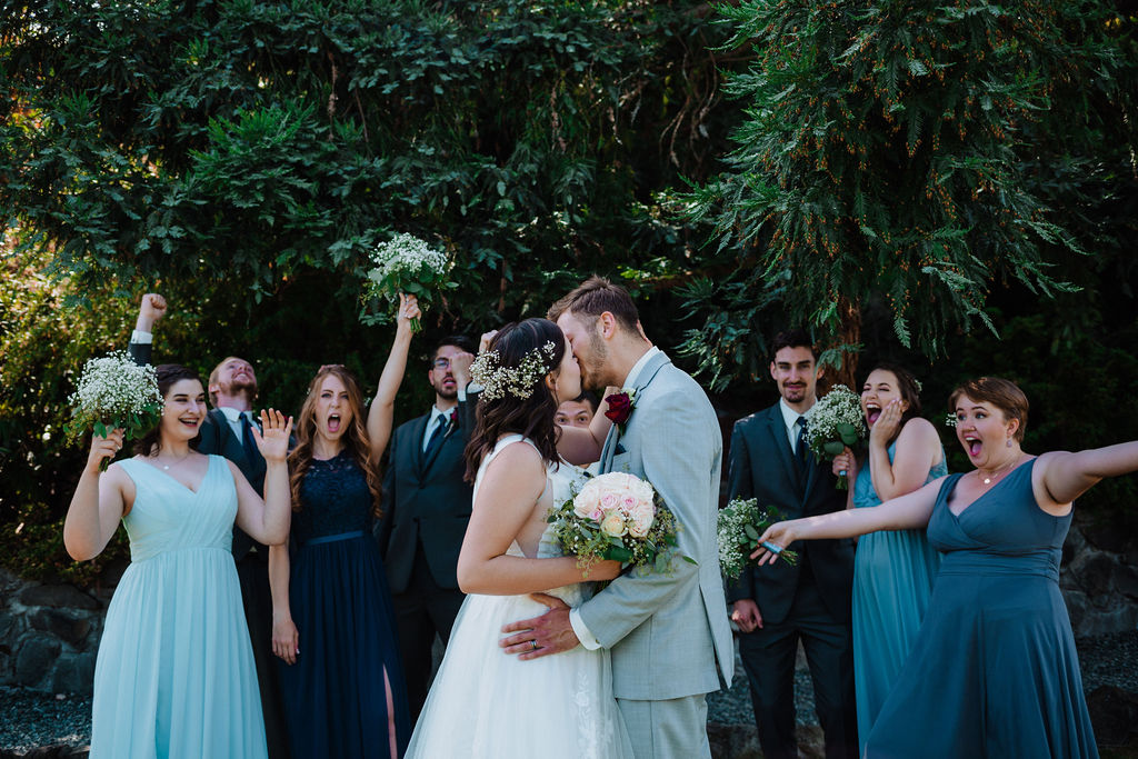 Newlyweds and bridal party laugh around the newlyweds kissing