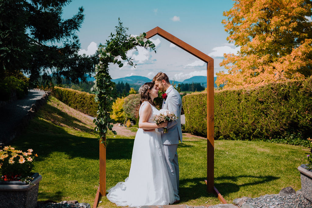Happily Ever After newlyweds framed by arch with floral design and mountains on Vancouver Island