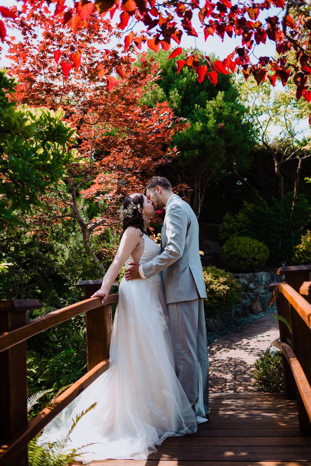 Happily Ever After Newlyweds kiss on Arbutus Ridge Garden Bridge on Vancouver Island