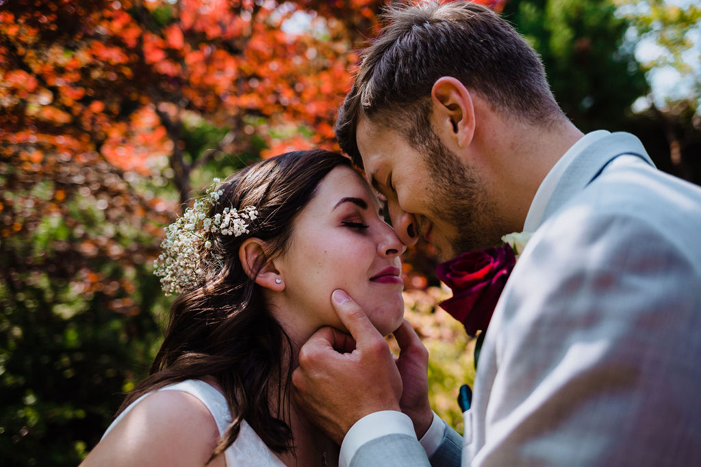 Newlyweds kiss in garden by Megan Maundrell PHotography