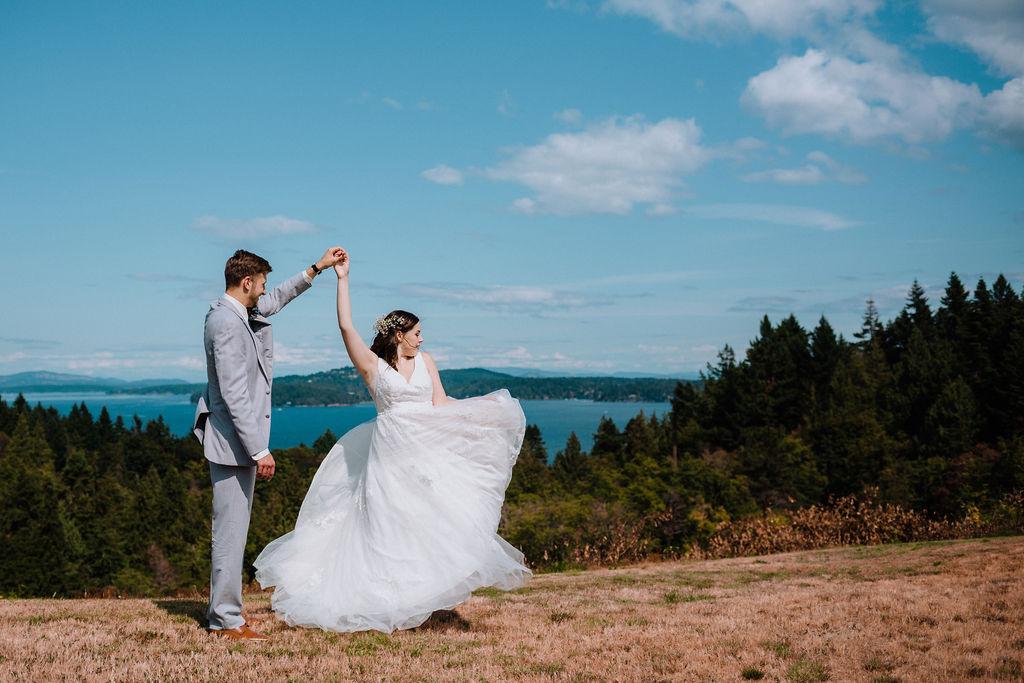 Groom twirls his bride along the ocean of Vancouver Island