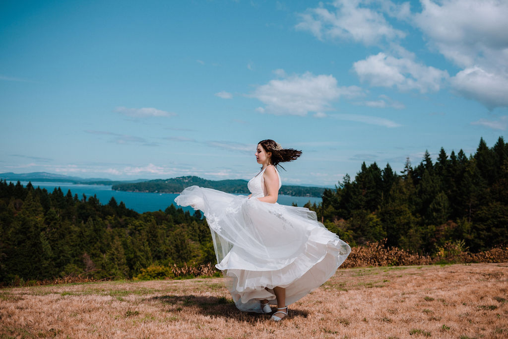Bride swirls her white gown skirt along the ocean edge of Vancouver Island