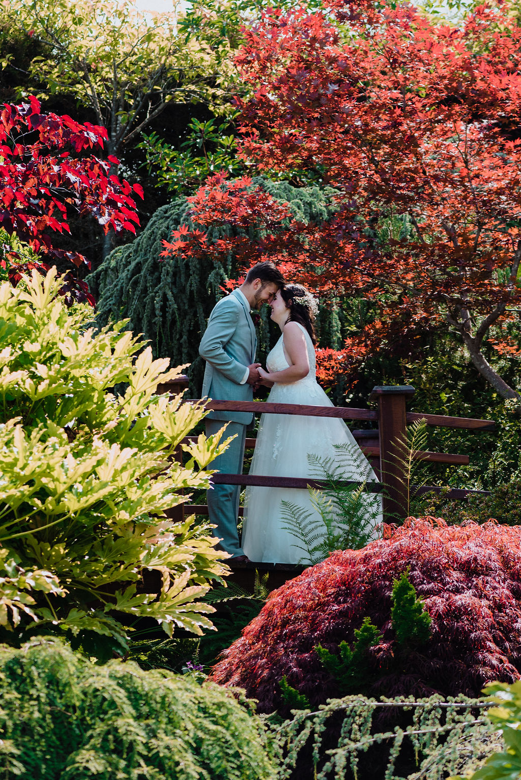 Newlyweds on foot bridge in garden of red and yellow bushes on Vancouver Island
