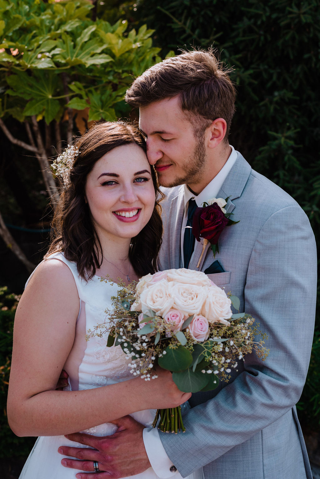 Bride smiles and holds bouquet while groom in grey suit holds her