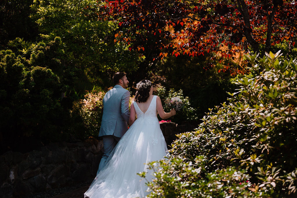 Bride with long flowing white gown with train in Arbutus Ridge gardens