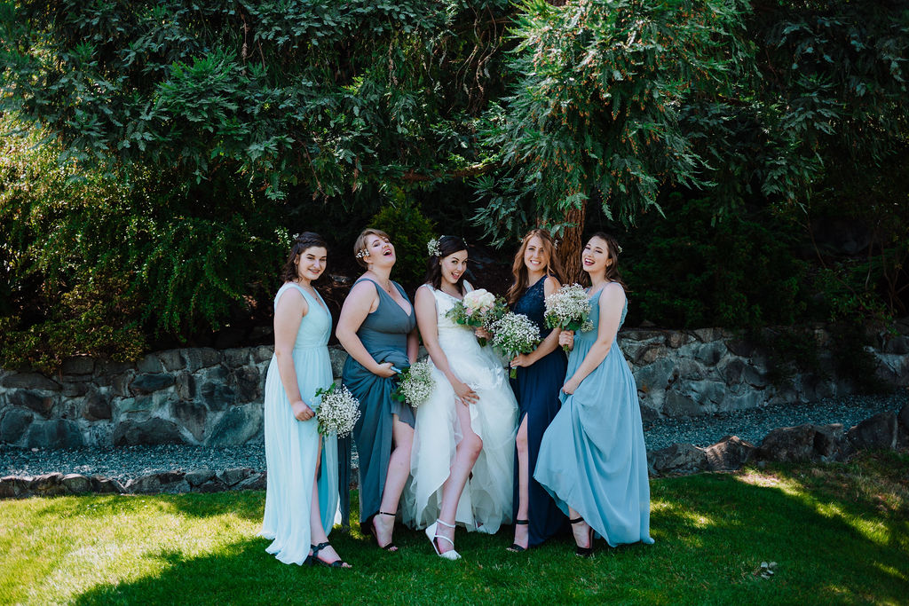 Bridesmaids in shades of blue and green dresses with bride