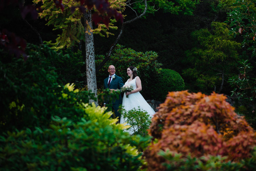 Bride is walked down garden steps to her ceremony at Arbutus Ridge