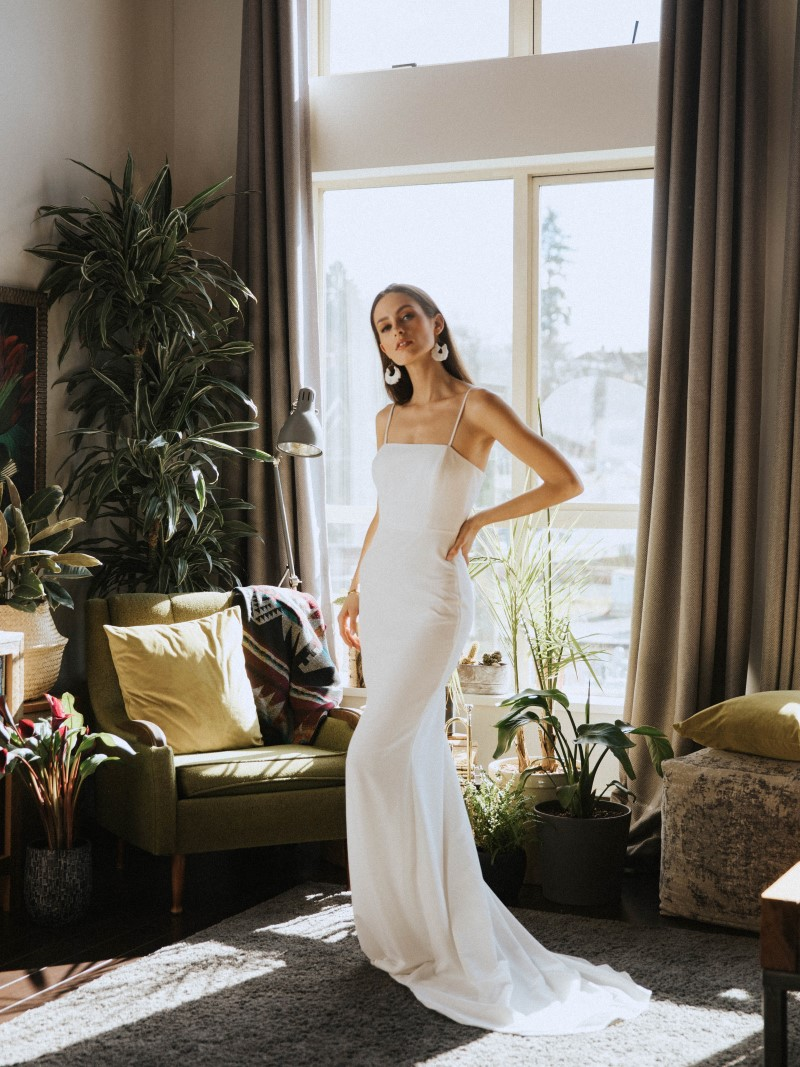 Bride in strapless gown in front of window